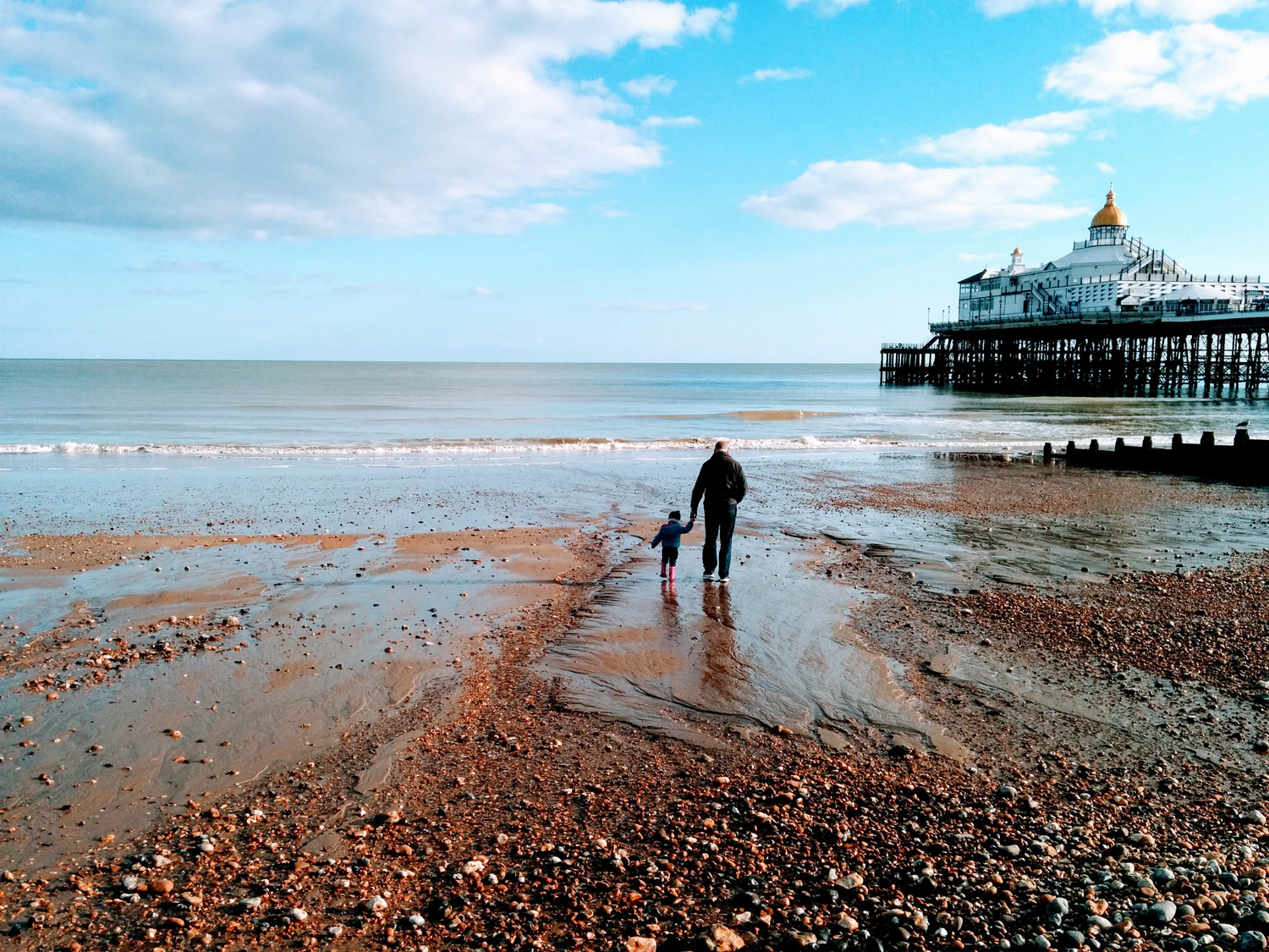 Nick and Hazel walk down the beach by Eastbourne pier at low tide